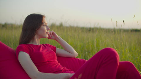 Tranquil pretty woman on beanbag relaxing in nature Live Action