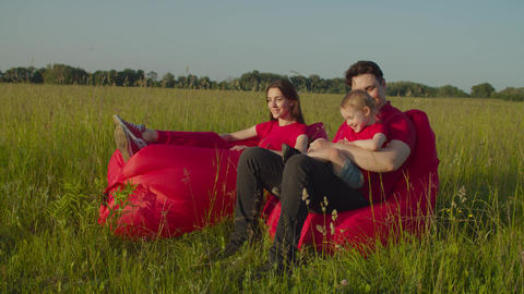Joyful parents with kid enjoying leisure in nature Live Action