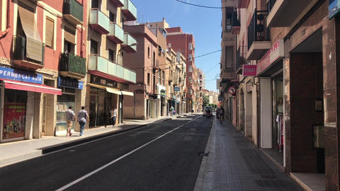 Reus, Spain, A narrow city street with buildings on the side of a building Live Action
