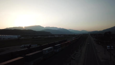 Twilight Over Freight Train in San Bernandino Valley, California, Aerial View Live Action