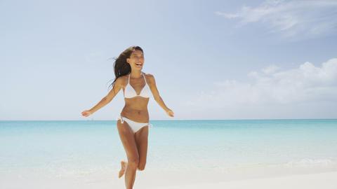 Beach bikini woman carefree running in freedom fun Live Action