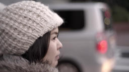 Slow-motion shot of young Japanese girl waiting to cross the road at zebra cross Footage