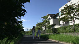 Japanese family walking in a residential area filled with green Footage
