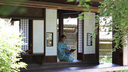 Mature Japanese woman in a kimono reading a book in a traditional house Footage