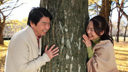 Japanese mature couple laughing by a tree in a city park in Autumn Footage