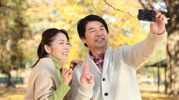 Japanese mature couple taking selfies in a city park in Autumn ภาพไม่มีลิขสิทธิ์