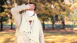 Japanese mature male wearing a mask feeling sick in a city park in Autumn Footage