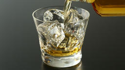 Close up shot of whiskey poured into glass with ice Footage