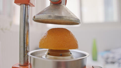 Super slow motion of fresh orange juice squeezed using a manual squeezer Live Action