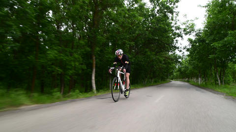 professional triathlete cycling road bike, sport concept, mountain road sunset Live Action