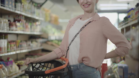 Unrecognizable smiling Caucasian woman posing with shopping basket in grocery Live Action