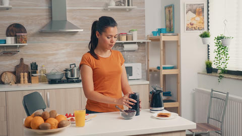 Cheerful wife grinding coffee beans Live Action