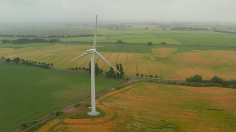 AERIAL: View of Foggy Agricultural Yellow Field with Single Wind Turbines Live Action
