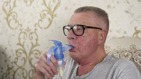 The old man in glasses is holding inhaler and breathes into it Live Action