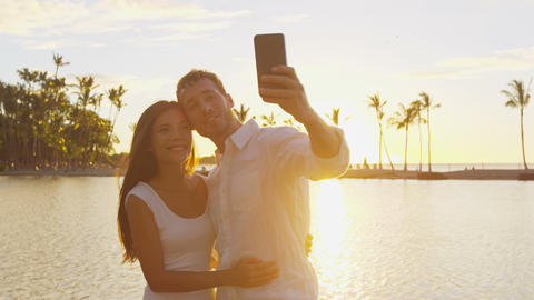 Selfie couple romantic at sunset on vacation taking photo in love at beach Live Action