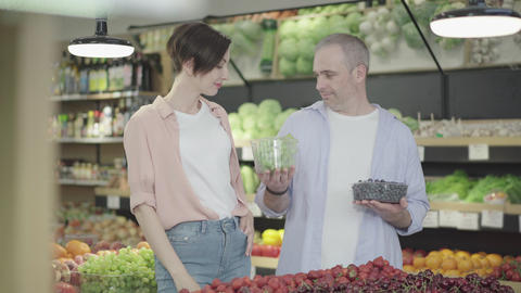 Happy family choosing grapes in grocery. Portrait of positive Caucasian man and Live Action