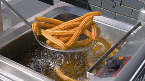 Slow motion: chef cooking churros in boiling oil at street food market: close up Live Action