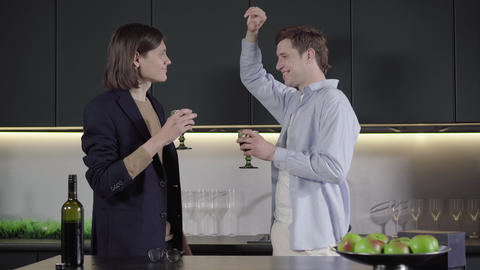 Cheerful gay couple dancing with wineglasses in the kitchen. Side view middle Live Action