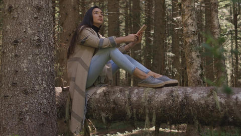 pretty woman using phone in forest sitting on wooden log Live Action