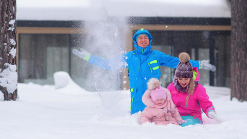 excited family sits in snow and throws up snow with laughter Live Action
