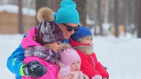 joyful man hugs wife and children sitting on snow closeup Live Action