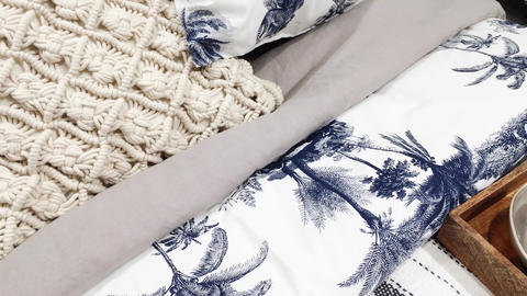 Bedding set and pillows on king size bed with a tropical motif as home decor in Live Action