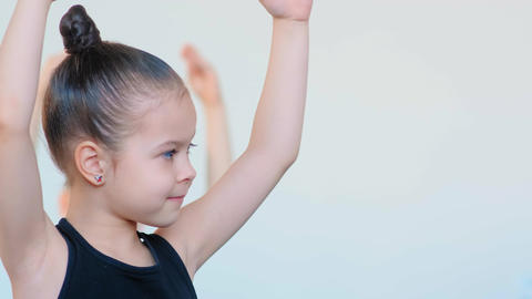small ballerina in black tracksuit exercises at class Live Action