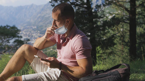 man taking off medical face mask and breathing air in mountains outdoors Live Action