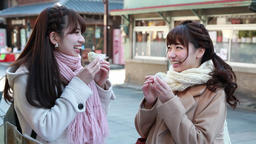 Young Japanese women eating a snack in Kawagoe, Saitama Prefecture, Japan Footage