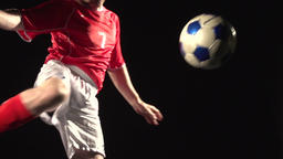 Slow-motion shot of Caucasian soccer player kicking the ball on a black backgrou Footage