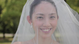 Attractive Japanese bride wearing wedding dress in a city park Footage