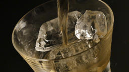 Pouring whiskey in a glass with ice Footage