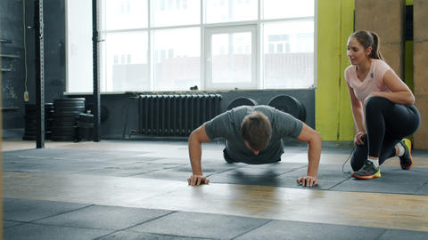 Young man doing push-ups exercising in gym with female coach enjoying exercise Live Action