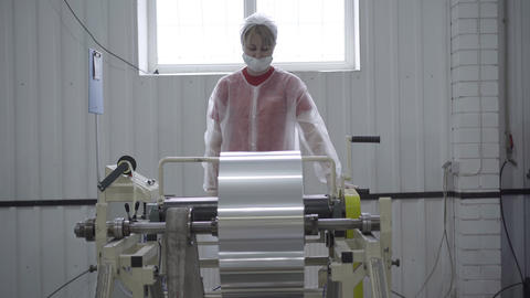 Young Caucasian woman in face mask and uniform controls process of aluminium Live Action
