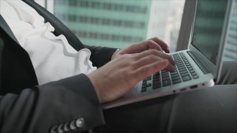 A businessman works behind a beech laptop in his office. Happy businessman Live Action