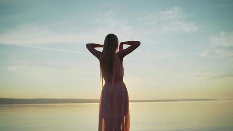 Girl in a light dress on the beach at sunrise. beautiful women in a light pink Live Action