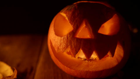Blinking candle light coming from traditional jack-o-lantern Live Action