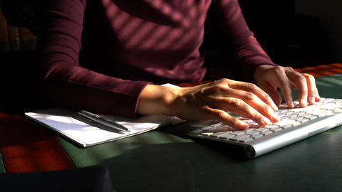 Woman typing on her computer keyboard at her work desk Live Action