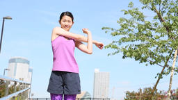 Young Japanese woman stretching before a run in the city Footage