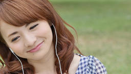 Young attractive Japanese woman listening to music in a city park GIF