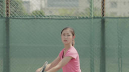 Young Japanese female tennis player in action on the court Footage