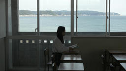 Japanese high-school student with book in an empty classroom Footage