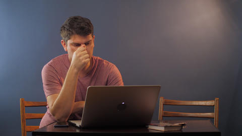concentrated person looks at laptop at small table in room Live Action