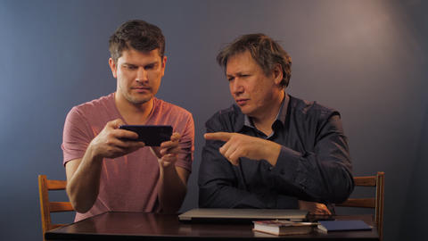mature man asks son how to use cellphone near at small table Live Action