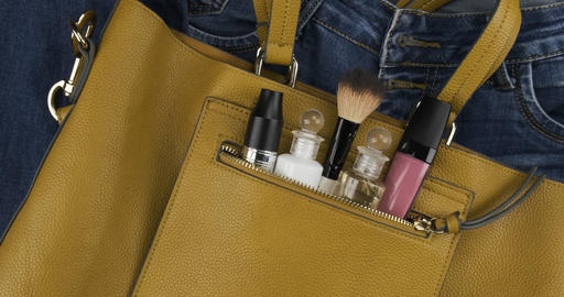 Cosmetics sticking out of the pocket of a yellow bag. Rotation. Cosmetic Live Action