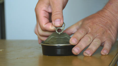 A man opens can of canned fish Live Action