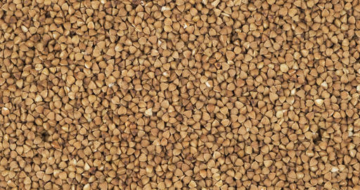 Buckwheat grain background, texture. Rotation and zoom out of grain background Live Action