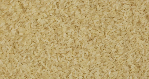 Whole rice grain background, texture. Rotation and zoom out of grain background Live Action