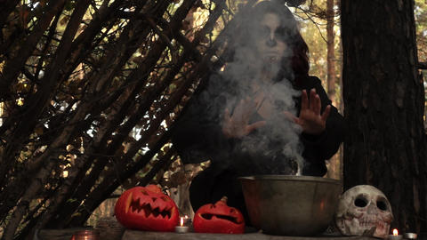 Witch brews a potion in a cauldron from which the smoke billows slow motion Live Action