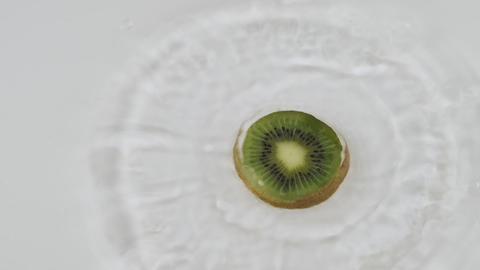 Fall of green slice of kiwi in white water. Slow motion Live Action